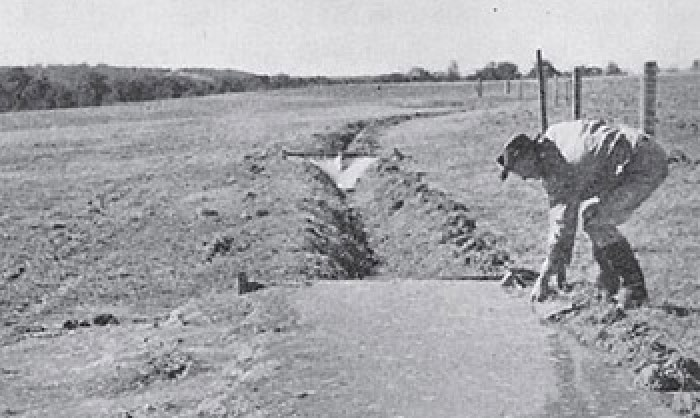 Black and white image of a man bending down and touching the soil.