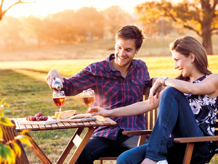 Man and women drinking wine outside.