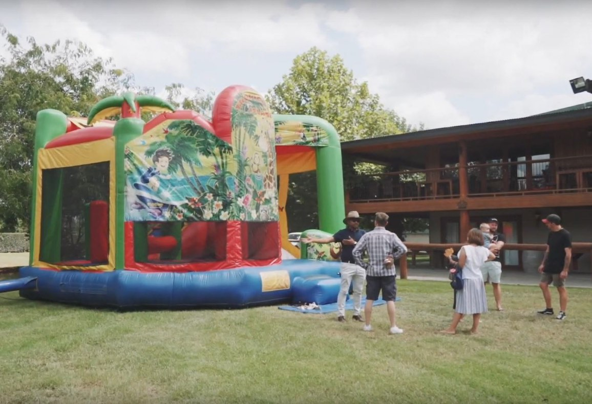 This image shows a number of adults and children surrounding a jumping castle at a social event.